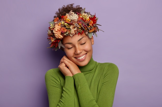 Urocza zadowolona jesienna dziewczyna opiera się o dłonie przyciśnięte do twarzy, przechyla głowę, nosi piękny wieniec z jesiennych roślin