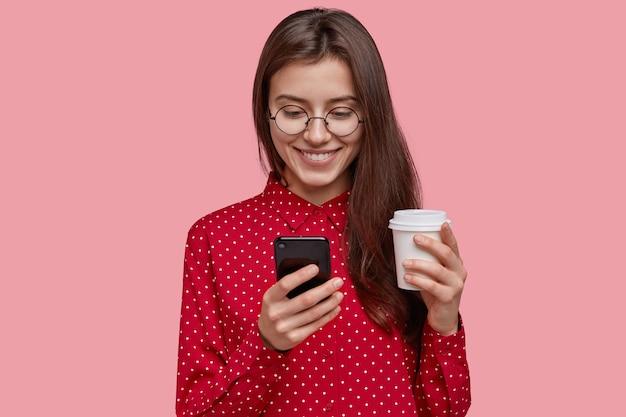 Urocza, zadowolona młoda kobieta trzyma gorącą kawę na wynos, telefon komórkowy, cieszy się, że otrzymuje nowe urządzenie jako prezent, nosi czerwoną koszulę, ma delikatny uśmiech