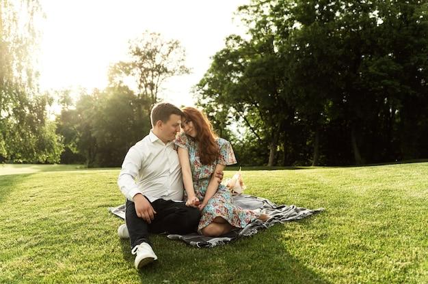 Urocza zakochana para urządziła sobie piknik w parku z wiklinowym koszem z kwiatami i jedzeniem na narzucie. szczęśliwi kochankowie śmieją się i jedzą na pikniku. romantyczna data