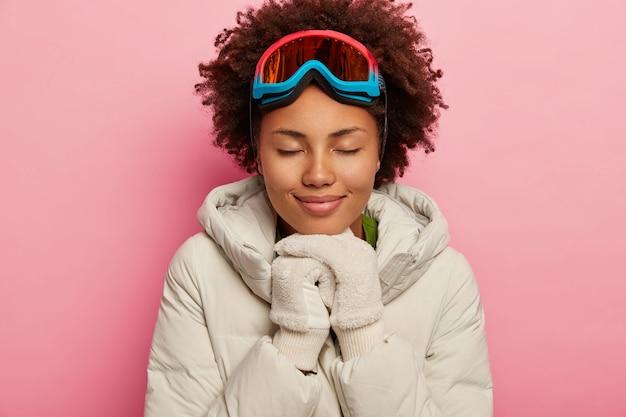 Urocza zdrowa kobieta o kręconych włosach, ubrana w biały puchowy płaszcz i rękawiczki, używa maski narciarskiej, z zamkniętymi oczami