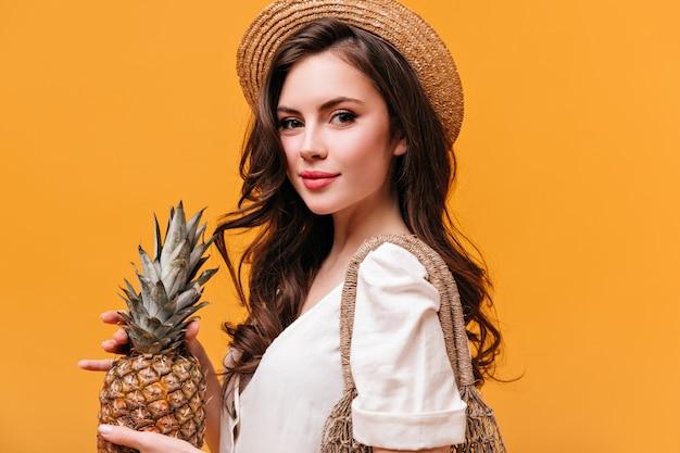 Urocza zielonooka brunetka kobieta w słomkowym kapeluszu, trzymając ananas i patrząc w kamerę na pomarańczowym tle.