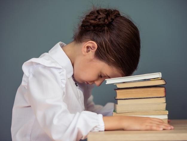 Urocza zmęczona dziewczynka w mundurek szkolny