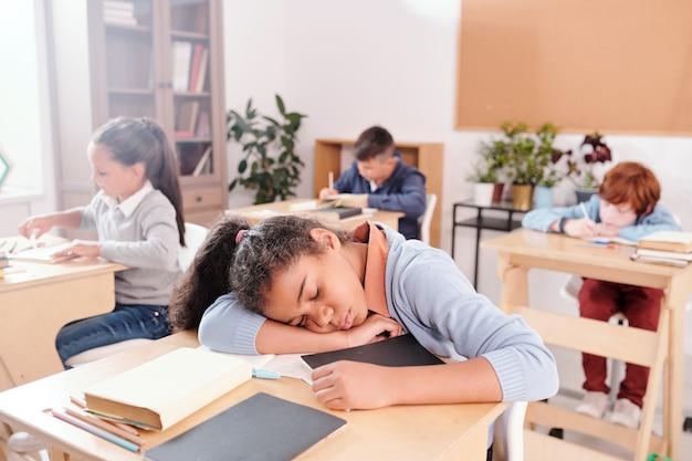Urocza zmęczona uczennica w stroju codziennym trzymająca głowę na biurku podczas drzemki na lekcji