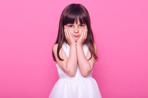 Urocza, znudzona mała dziewczynka patrzy z przodu ze zmęczonym wyrazem twarzy, trzymając ręce na policzkach, nie wie, co robić, ubrana w piękną białą sukienkę, odizolowana na różowej ścianie