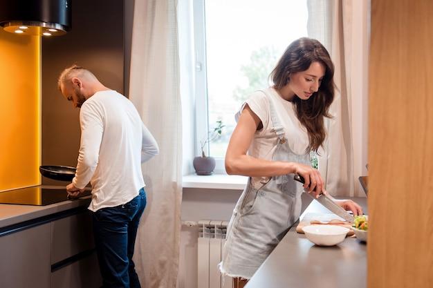 Urocza żona o ciemnych włosach ścina świeże warzywa na drewnianej desce, podczas gdy jej brodaty mąż stawia patelnię na kuchence gazowej