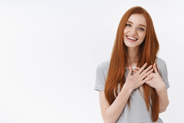 Urocza żywa delikatna kobieca młoda rudowłosa dziewczyna flirtuje spojrzenie zadowolona śmiejąca się radośnie trzymaj dłonie przyciśnięte do piersi rozgrzewający gest dotknięta, zachwycona szczerze uśmiechnięta