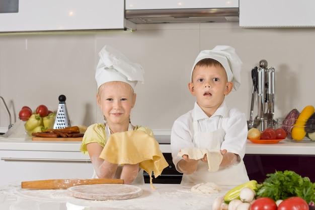 Urocze białe dzieciaki w strojach szefów kuchni przygotowujących jedzenie na przekąski w kuchni.
