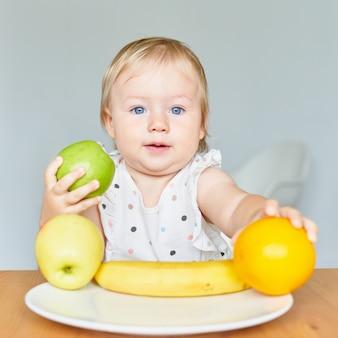 Urocze blond niebieskookie dziecko trzymające zielone jabłko i pomarańczowy talerz z owocami