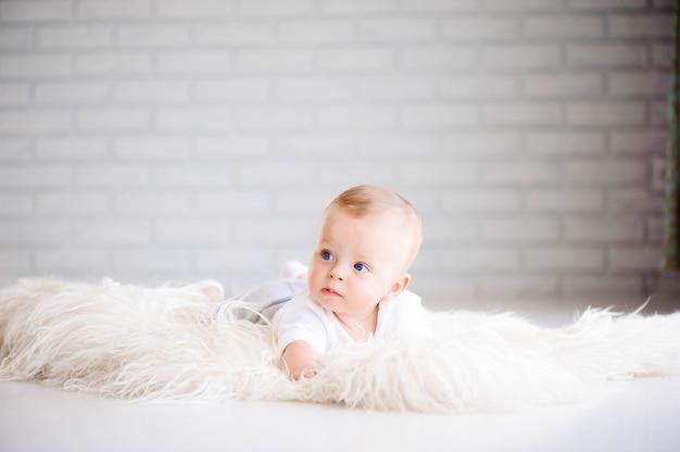 Urocze chłopczyk uczący się raczkować i bawić się w białej słonecznej sypialni