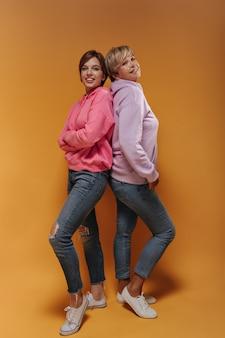 Urocze dwie kobiety z nowoczesnymi krótkimi fryzurami w szerokiej modnej bluzie z kapturem i obcisłych fajnych dżinsach uśmiechniętych na odosobnionym tle.