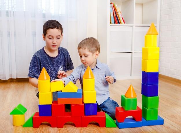 Urocze dzieci bawiące się z konstruktorem na podłodze w domu. dzieci w wieku przedszkolnym zabawy. żłobek, rozwój dzieci. na podłodze kolorowe plastikowe klocki.