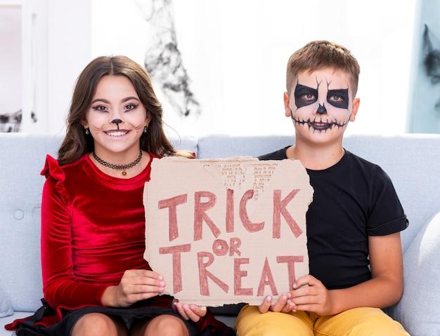 Urocze dzieci trzymając znak cukierek albo psikus
