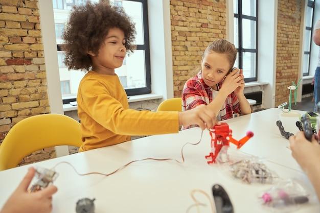 Urocze dzieciaki siedzące przy stole i badające szczegóły technicznych zabawek podczas lekcji łodyg