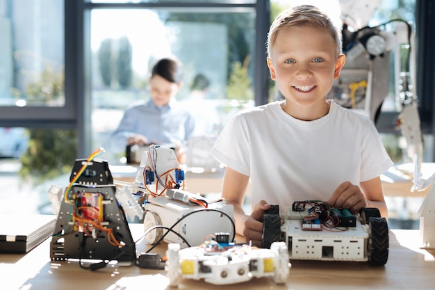 Urocze dzieciaki w wieku przedszkolnym oglądające warsztat pojazdów robotów