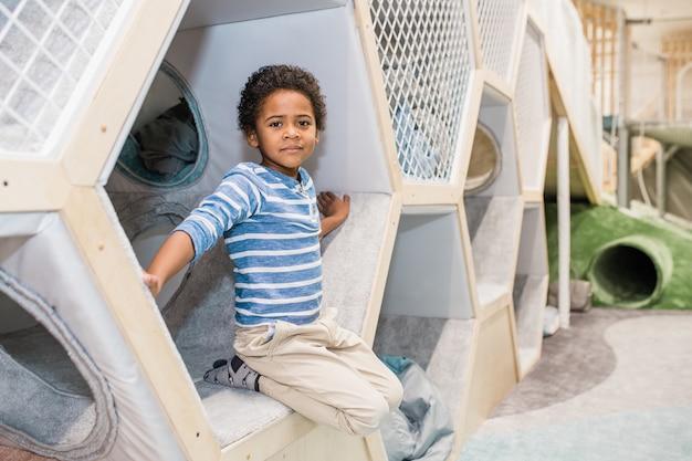 Urocze dziecko afrykańskiego pochodzenia w wieku przedszkolnym, ubrane w koszulę i dżinsy, patrząc na ciebie na placu zabaw w centrum dziecięcym