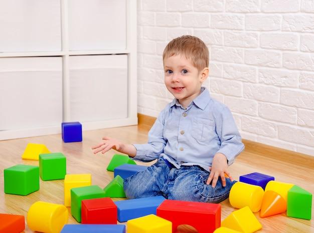 Urocze dziecko bawi się z konstruktorem na podłodze w domu. dzieci w wieku przedszkolnym zabawy. żłobek, rozwój dzieci. na podłodze kolorowe plastikowe klocki.