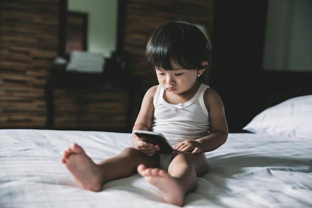Urocze dziecko grające telefon komórkowy w sypialni