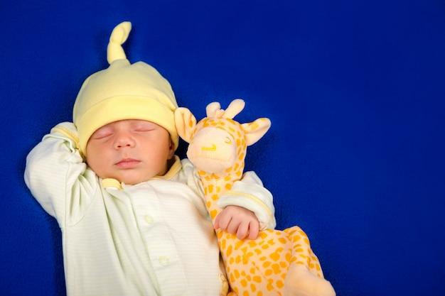 Urocze dziecko leżące na niebieskim kocu z zabawkową żyrafą. chłopiec czy dziewczyna