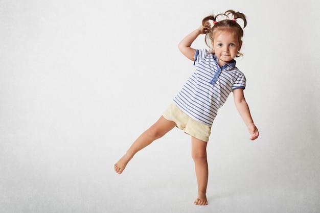 Urocze dziecko ma zabawny wyraz, dwa ogony kucyka, nosi koszulkę i spodenki casaul, stoi na jednej nodze