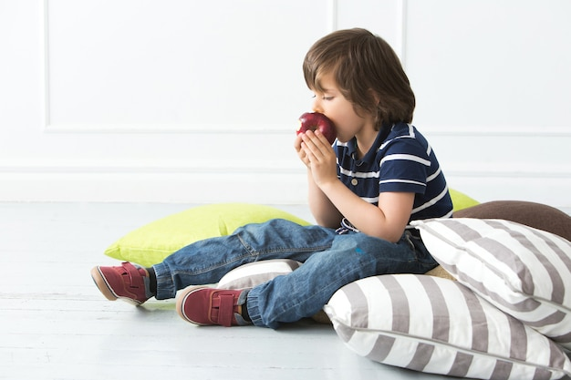 Urocze dziecko na podłodze, jedzenie jabłka