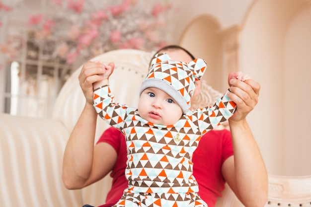Urocze dziecko rasy kaukaskiej i jego ojciec. portret trzymiesięcznego chłopca.
