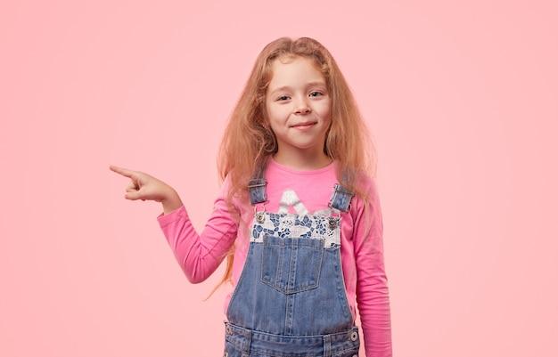 Urocze dziecko treści w dżinsowym kombinezonie wskazującym palcem wskazującym