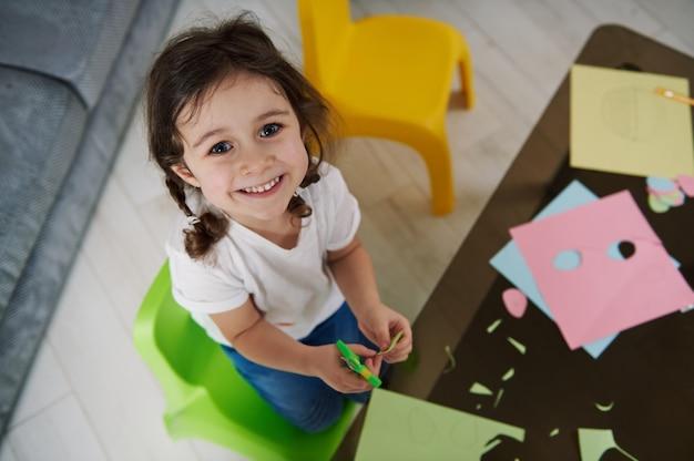Urocze dziecko trzymające nożyczki, tnące kolorowy papier i słodkie uśmiechy do aparatu.