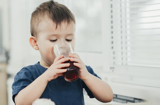 Urocze dziecko w kuchni latem napój z granatu lub soku wiśniowego koloru czerwonego