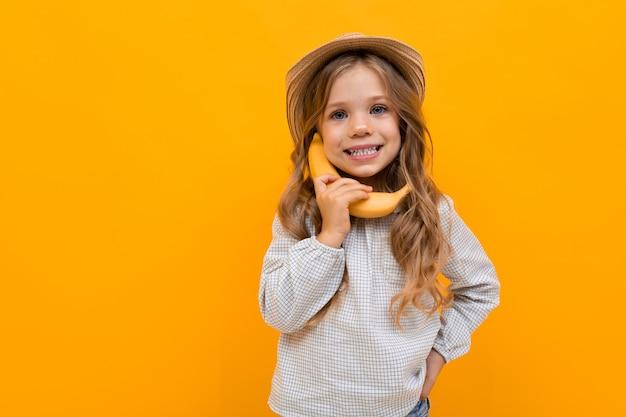 Urocze dziecko w letnim kapeluszu rozmawia na bananie jak odbiornik telefonu operacyjnego na żółtym tle