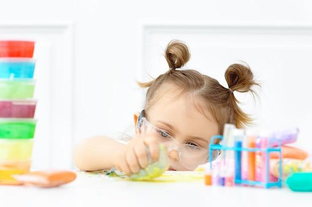 Urocze dziecko w ochronnych okularach uczy się chemii i robi w klasie puszysty szlam z różnobarwnych składników