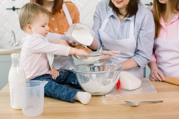 Urocze dziecko z matką, ciotką i babcią, które wspólnie robią ciasto z mąki, jajka i cukru. kobiety w białych fartuchach i czapkach szefów kuchni zraszające ciasto na ciasto z mąką na stole