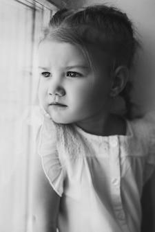 Urocze dziecko z warkoczem, patrząc przez okno