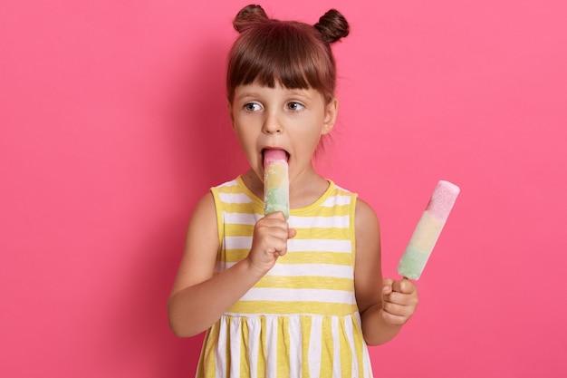 Urocze dziecko żeńskie gryzące lody wodne i spoglądające na bok, dziewczyna z dwoma węzłami, ubrana w letnią sukienkę, pozująca odizolowana na różowym tle, stoi z sorbetami w rękach.