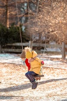 Urocze dziewczynki bawią się na huśtawce w central parku w nowym jorku