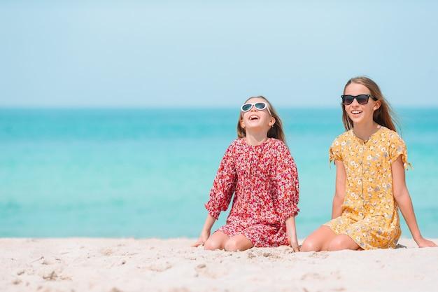Urocze dziewczynki bawią się na tropikalnej plaży podczas wakacji
