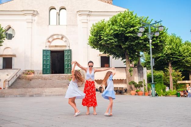 Urocze dziewczynki i młoda matka bawią się we włoskiej starej wiosce