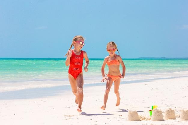 Urocze dziewczynki podczas letnich wakacji. dzieci bawiące się zabawkami na plaży na białej plaży