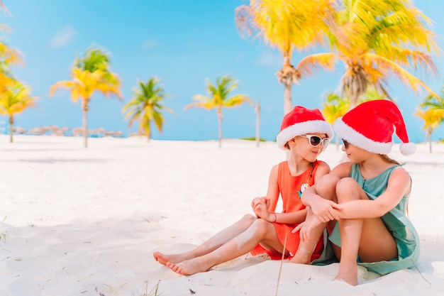 Urocze dziewczynki w czapkach świętego mikołaja podczas świątecznych wakacji na plaży, wspólna zabawa