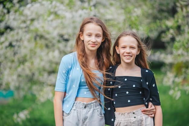 Urocze dziewczynki w kwitnącym ogrodzie jabłoni w wiosenny dzień