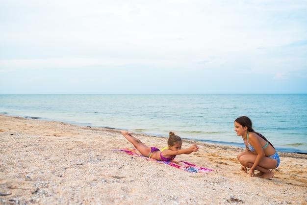 Urocze dziewczynki wykonują ćwiczenia gimnastyczne, relaksując się na plaży w słoneczny, ciepły letni dzień