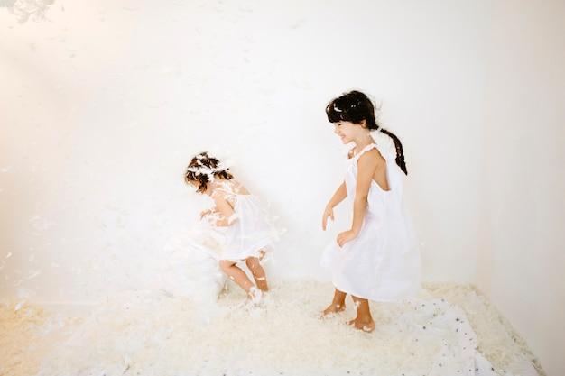 Urocze dziewczyny bawiące się na materacu