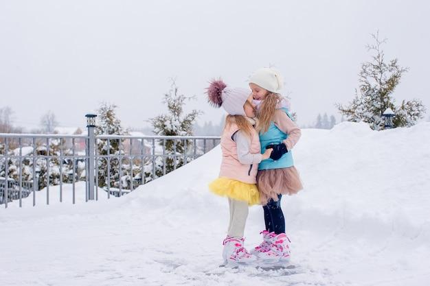 Urocze dziewczyny na łyżwach na lodowisku na zewnątrz w zimowy dzień śniegu