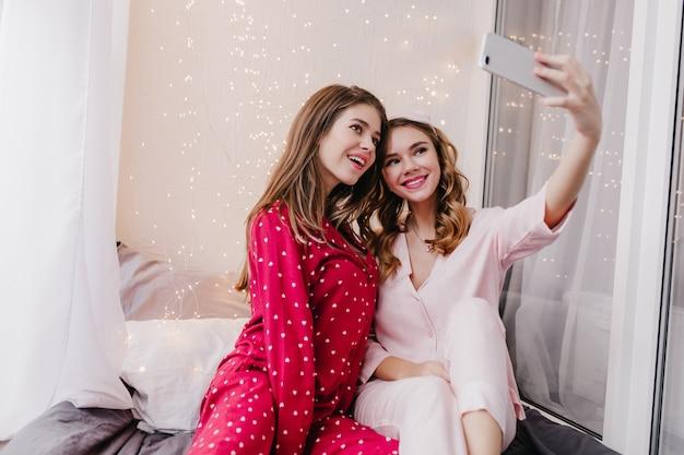 Urocze dziewczyny siedzą na łóżku i pozują do selfie. wewnątrz zdjęcie dwóch zrelaksowanych młodych kobiet cieszących się razem dzień dobry.
