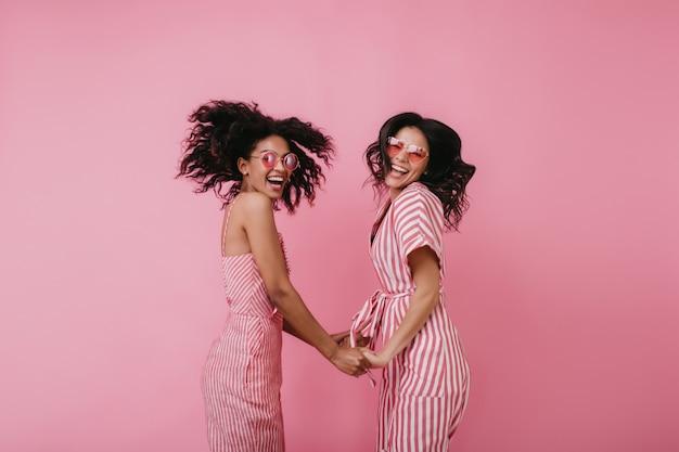 Urocze dziewczyny w czarujących okularach śmieją się razem. wewnętrzne zdjęcie niesamowitych międzynarodowych przyjaciółek trzymających się za ręce i tańczących.