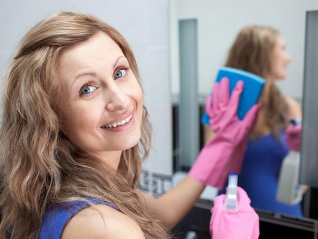 Urocze kobiety czyszczenia lustro łazienkowe