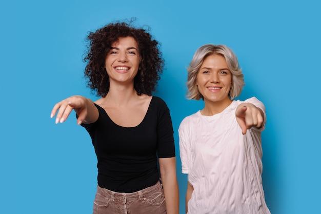 Urocze kobiety w zwykłych ubraniach wskazują na uśmiechniętą kamerę na niebieskiej ścianie z wolną przestrzenią