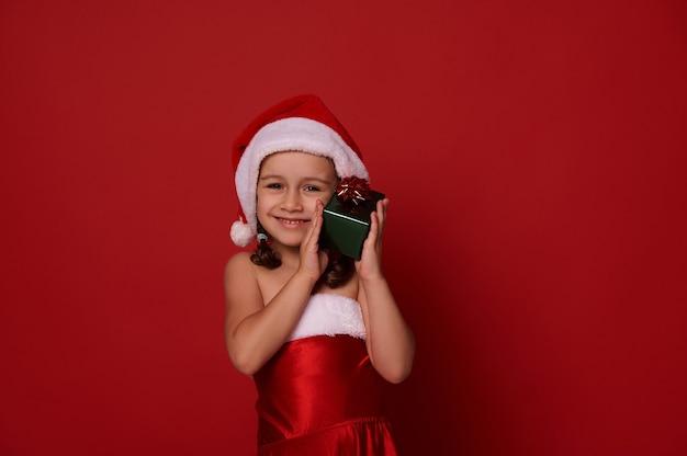 Urocze ładne dziecko, wspaniała mała dziewczynka w stroju na karnawał w santa delikatnie przytula swoje świąteczne pudełko w brokatowym zielonym papierze do pakowania i czerwoną kokardką, uroczo uśmiecha się patrząc w kamerę. skopiuj miejsce na reklamę