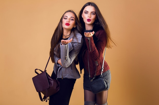 Urocze, ładne kobiety całują się i noszą zwykłe zimowe kurtki