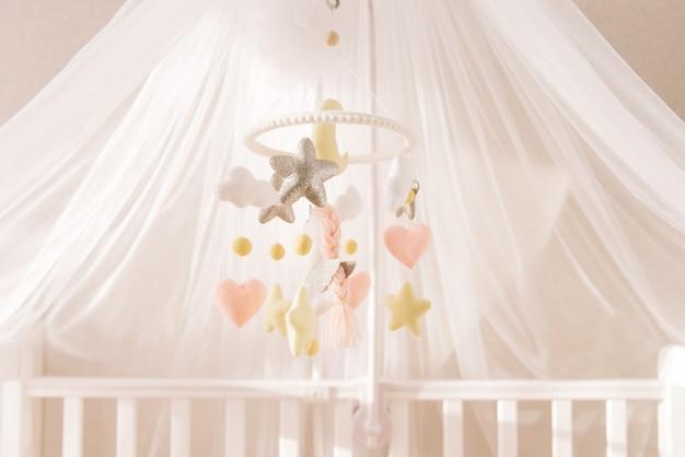 Urocze łóżeczko dla dziewczynek w kolorze różowym z ręcznie robionymi ruchomymi zabawkami z filcu