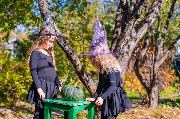 Urocze małe czarownice bawią się na zewnątrz w halloween. cukierek albo psikus.